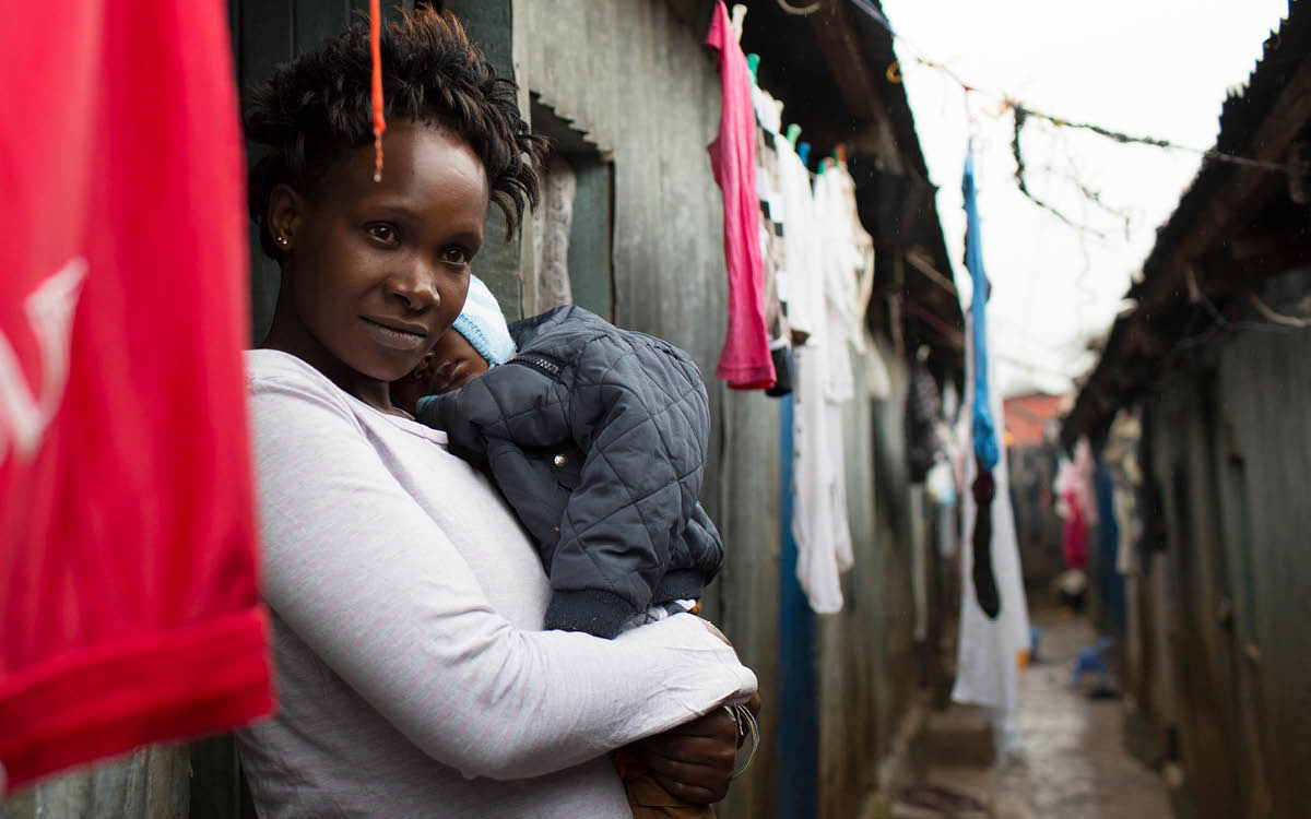 Emilie Auma Otieno with her son Lourance in front of their hut in Kawangare slum.